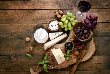 Artistic arrangement of cheeses, grapes, dried fruit, red wine and beautiful curved dark wooden board