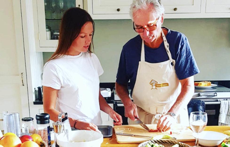Woman and elderly man working at a kitchen worktop