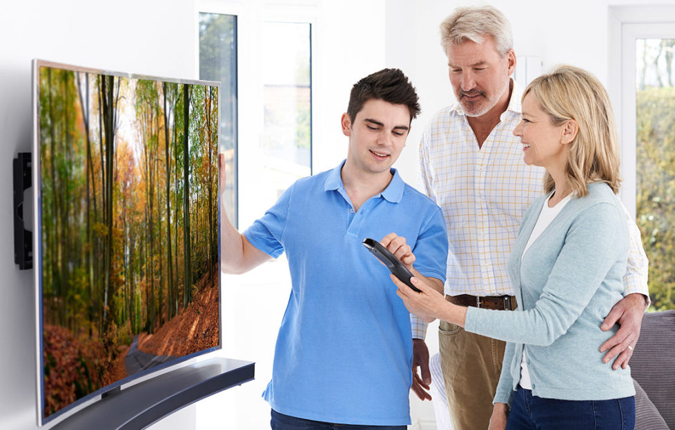Buy laUse a credit card for large purchases. Man Demonstrating New Television To Mature Couple At Home