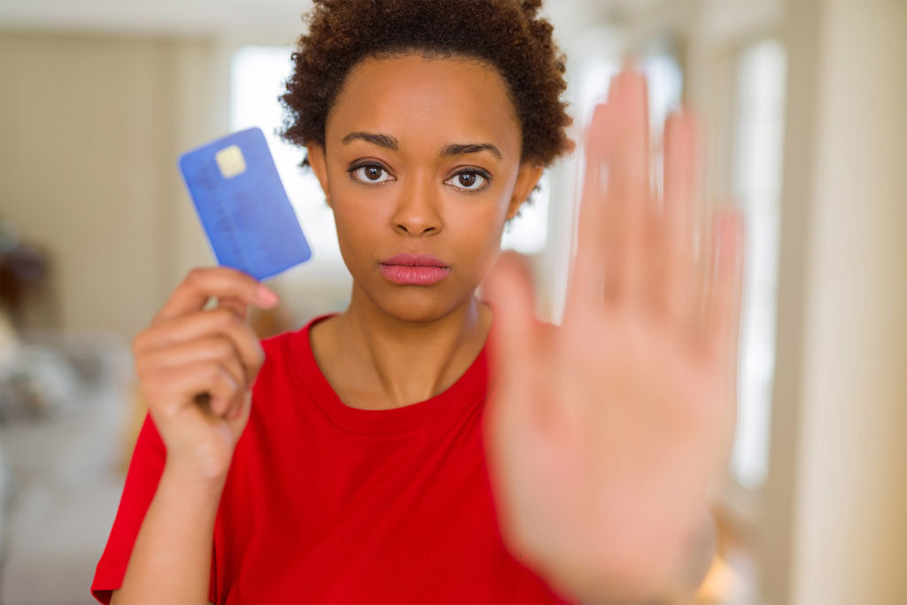 Woman holding credit card, other hand up in a Stop gesture