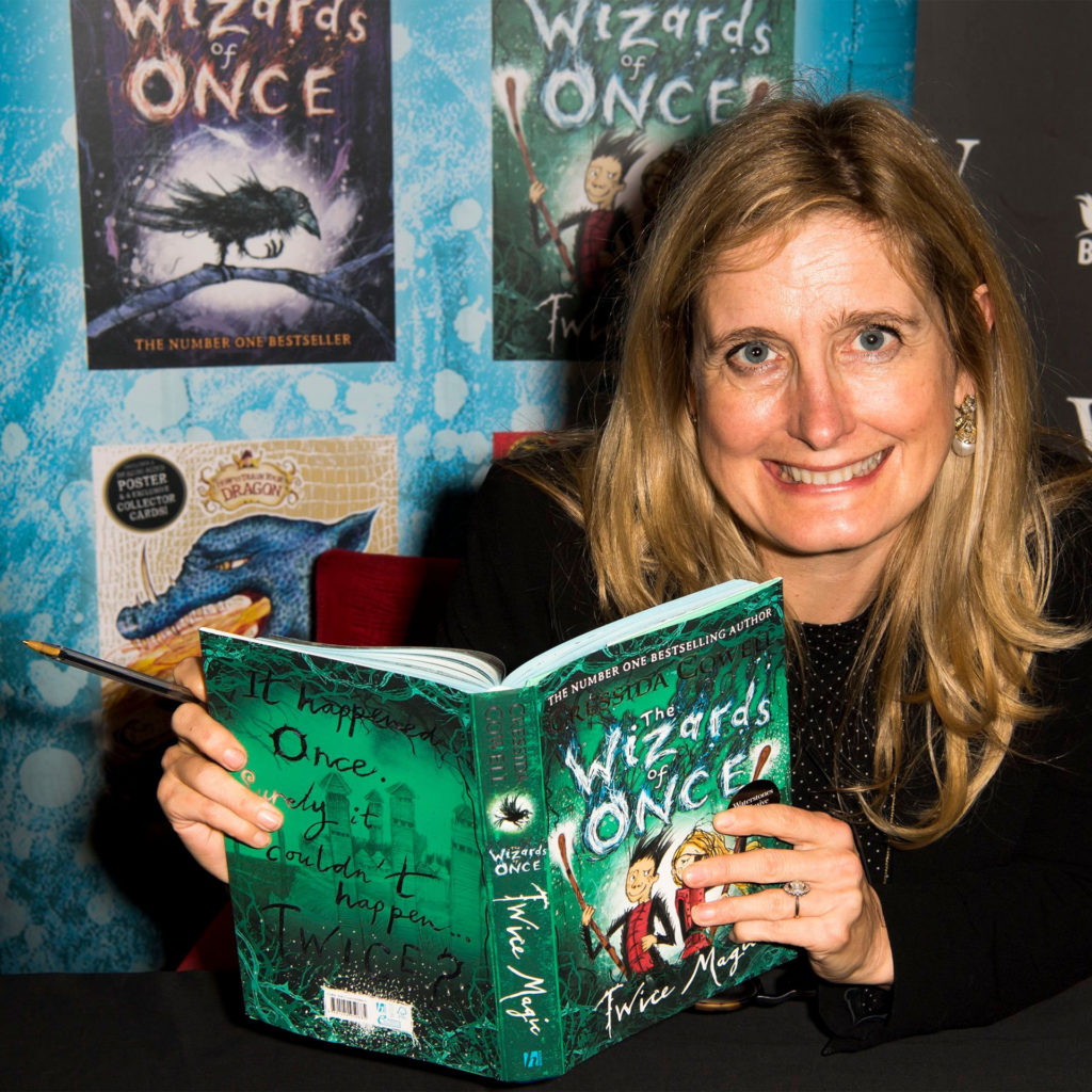 Author Cressida Cowell at an event for her book The Wizards of Once, looking lively, holding book and a pen