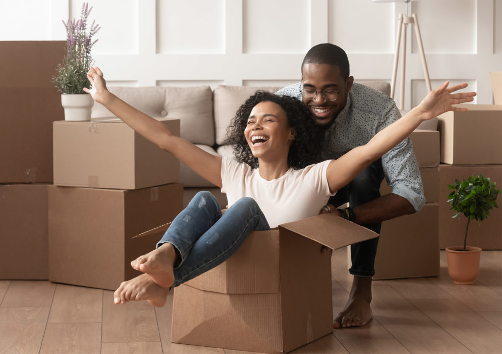 Happy young couple in first home, she is sitting in a packing box and he is pushing it along