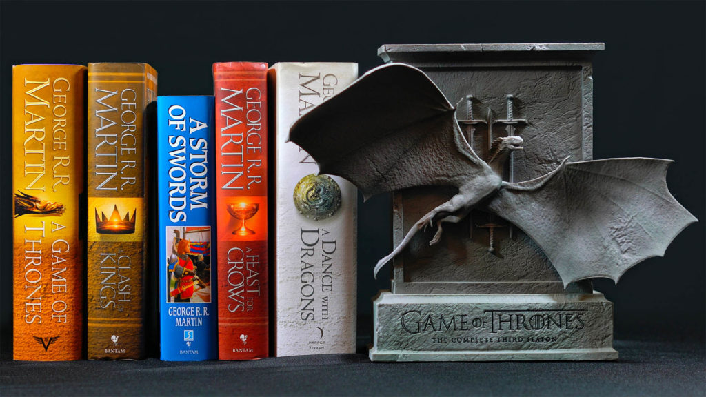 Set of Game Of Thrones books by George Martin standing in a row with special edition DVD set in metal effect box with flying dragon sculpture attached to the front