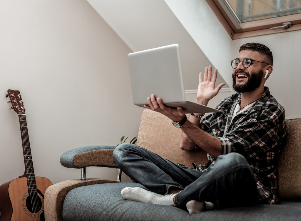 Friendly bearded man sitting cross legged in attic room, waving at person on laptop screen