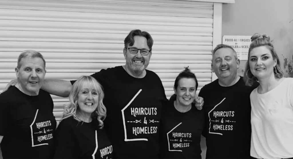 6 smiling people, 5 in black t shirts branded Haircuts 4 Homeless, standing in front of shop shutter