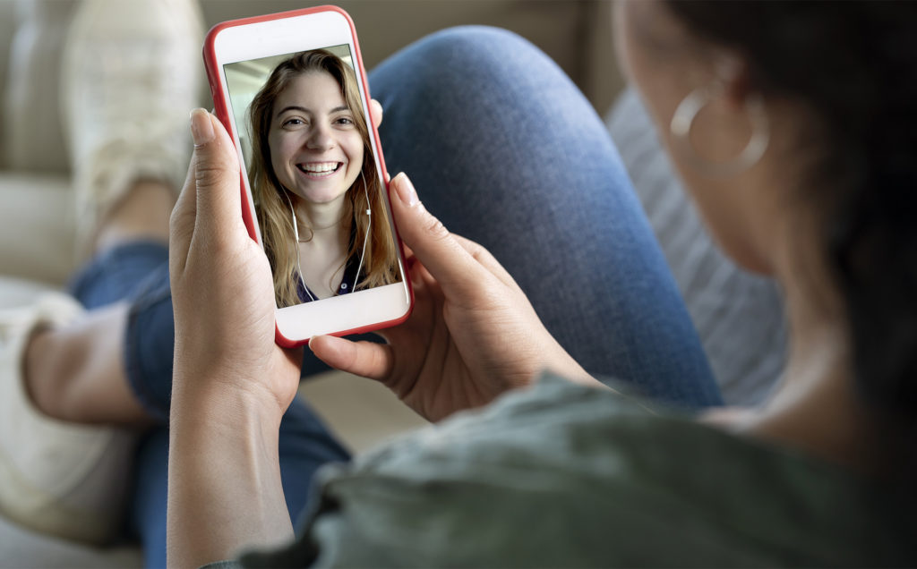 Smiling young woman on phone screen