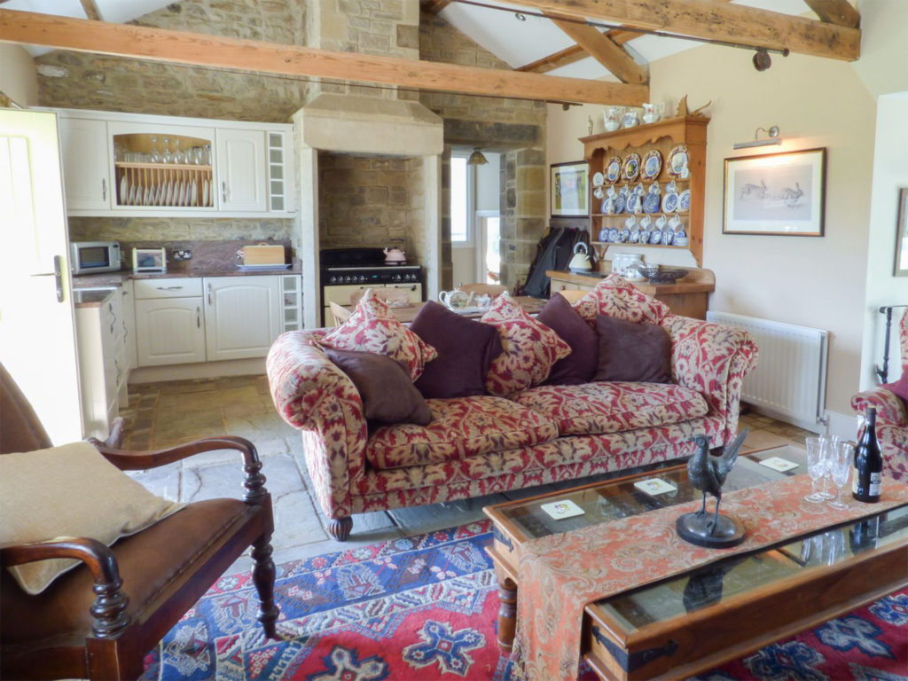 Cottage living room with chintz sofa and dresser with plates, kitchen behind