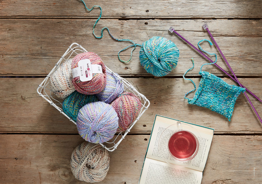 Basket of yarn balls, square knitted in turquoise on knitting needles, also glass of juice and open book