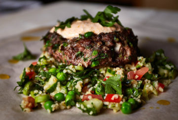 Juicy lamb kofta burger topped with rose yogurt and herbs, sitting on pile of tabbouleh, grains, chopped herbs and salad veg.