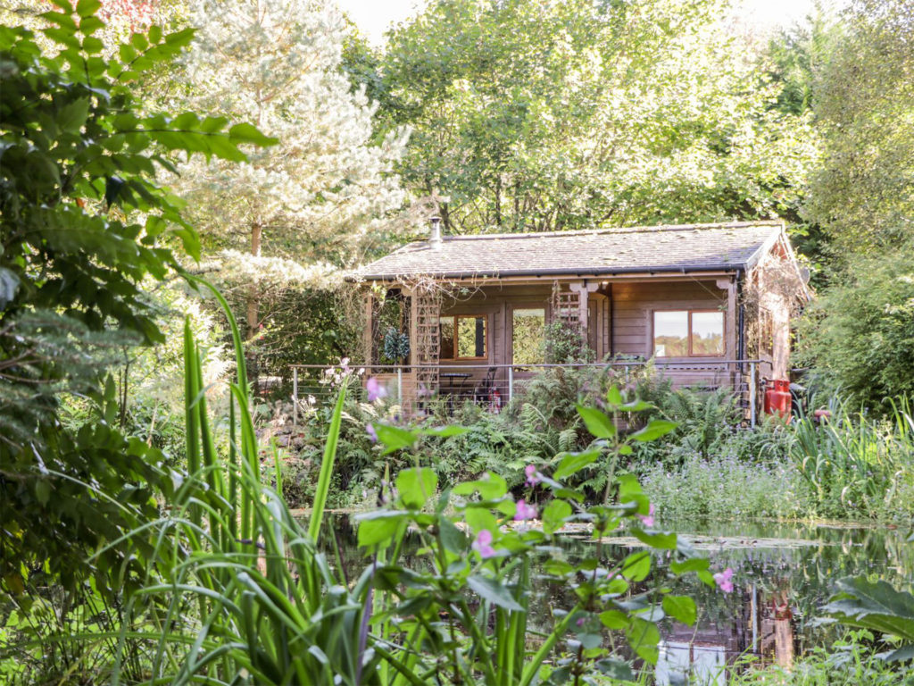 Log cabin set in trees and luxuriant garden with pond