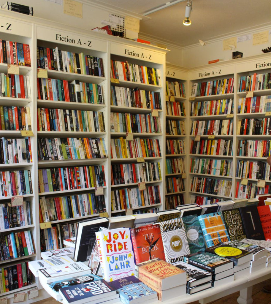Interior of Mr B's Emporium, bright modern bookshop with tall white shelves and more books on a table