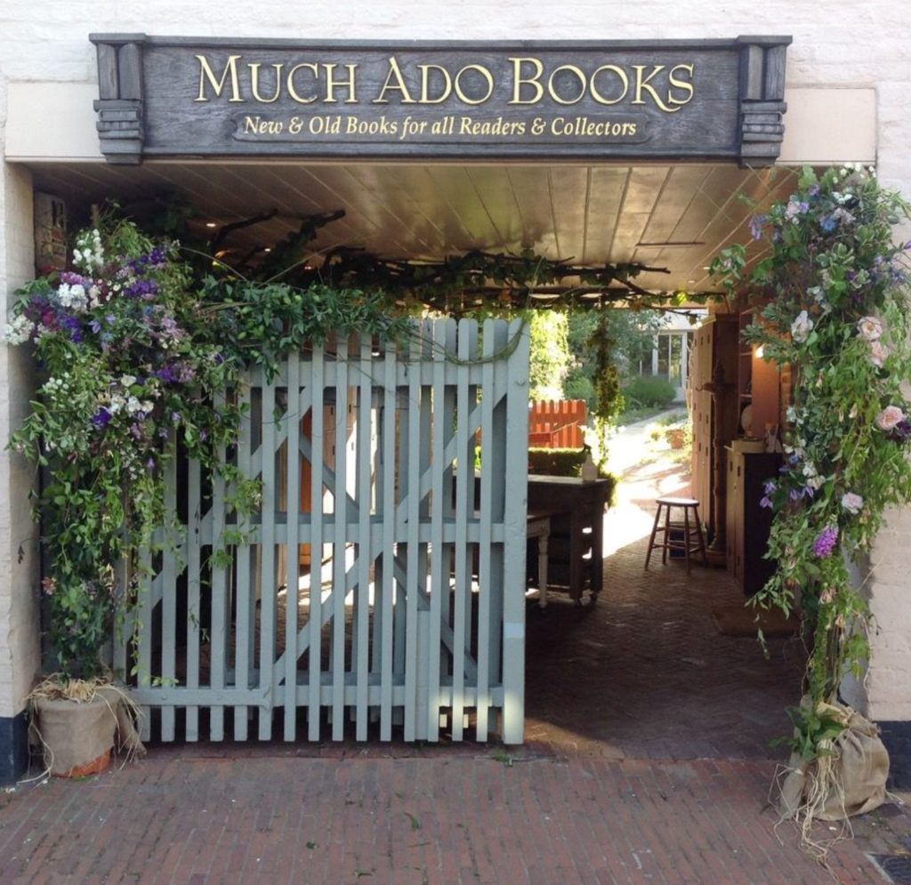 Much Ado bookshop entrance, with sage green painted wooden gate and plants around walls