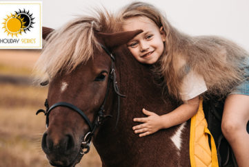 Girl on Shetland pony's back, leaning forward to hug it