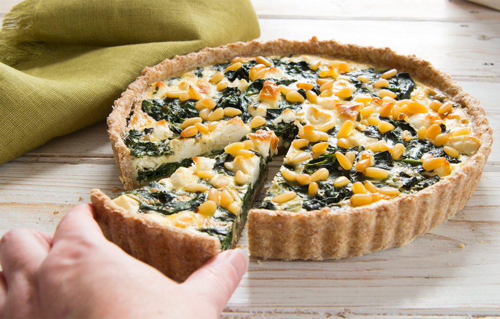 Feta quiche containing spinach and pine nuts, hand taking one cut slice