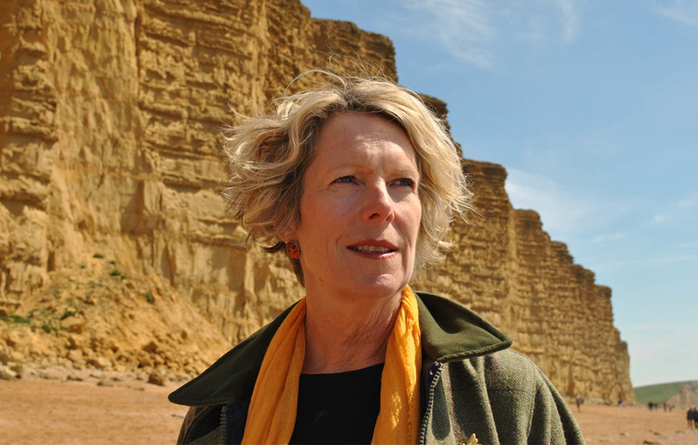 Author Rosanna Ley, blonde middle aged woman in rich yellow scarf and green walking jacket standing by yellow cliffs