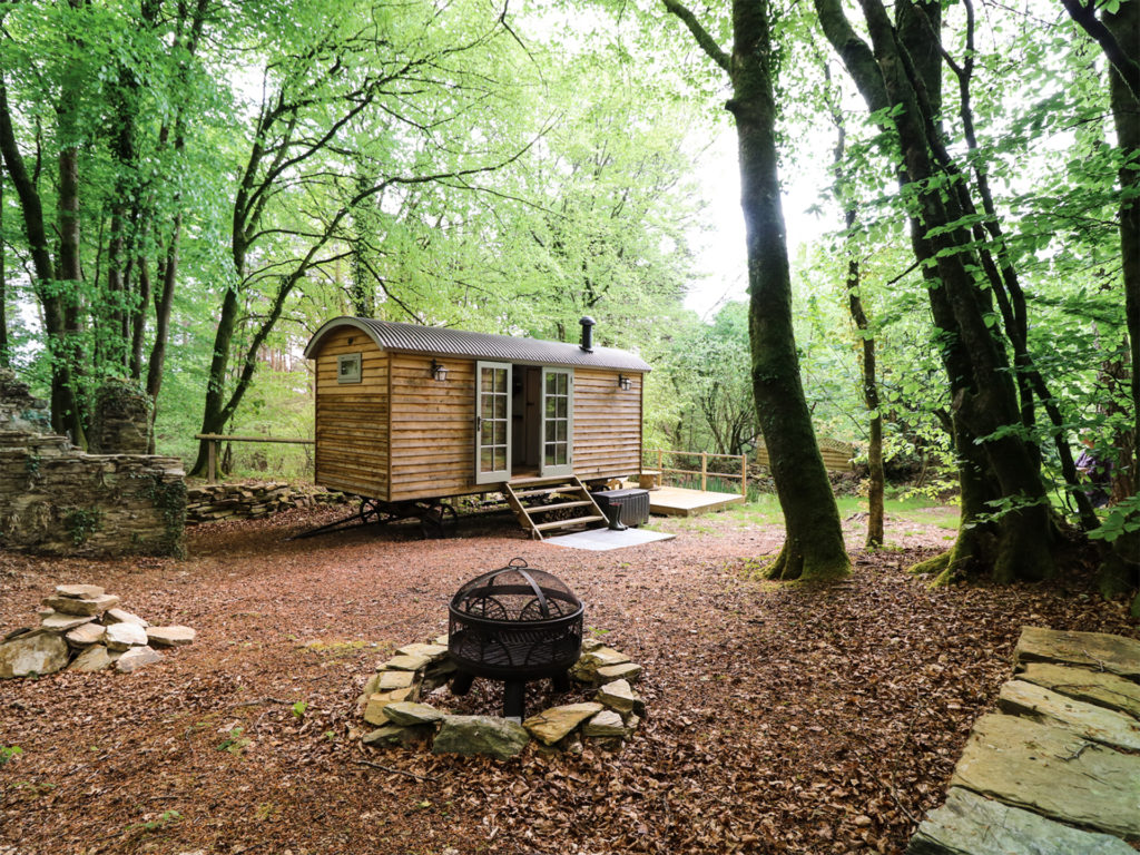 Converted wooden shepherd's hut on wheels in woodland clearing with fire pit