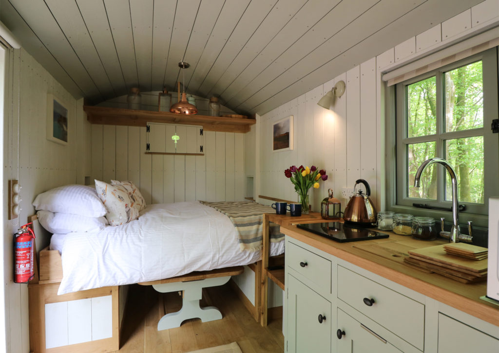 Interior of shepherd's hut, kitchen in middle and cosy double bed pulled out over table at one end