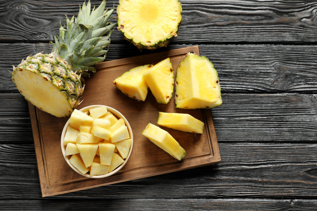Wooden board with fresh sliced pineapple on table, top view;