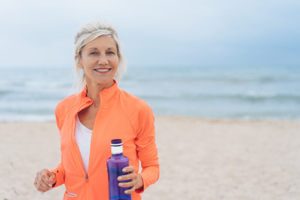 Vivacious fit woman walking on a beach in colorful sportswear carrying a blue bottle of water smiling at the camera;