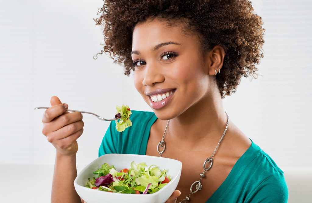 Close-up Of Beautiful African American Woman Eating Salad At Home;