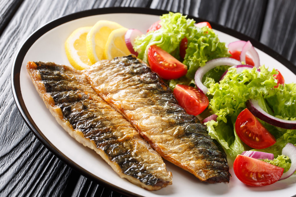 Portion of grilled mackerel fillet with lemon and fresh vegetable salad close-up on a plate on the table. horizontal ;