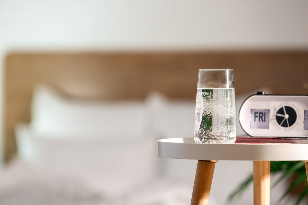 Glass of water and alarm clock on table in bedroom;