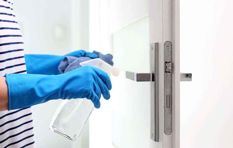 Cleaning the house, cleaning door handles. Prevention and prevention of infection. The woman cleans the apartment