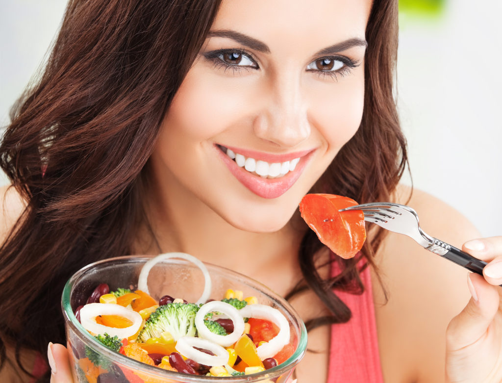 Portrait of happy smiling young brunette woman with vegetarian vegetable salad;