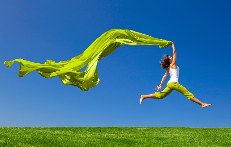 Beautiful young woman jumping on a green meadow with a coloured tissue;
