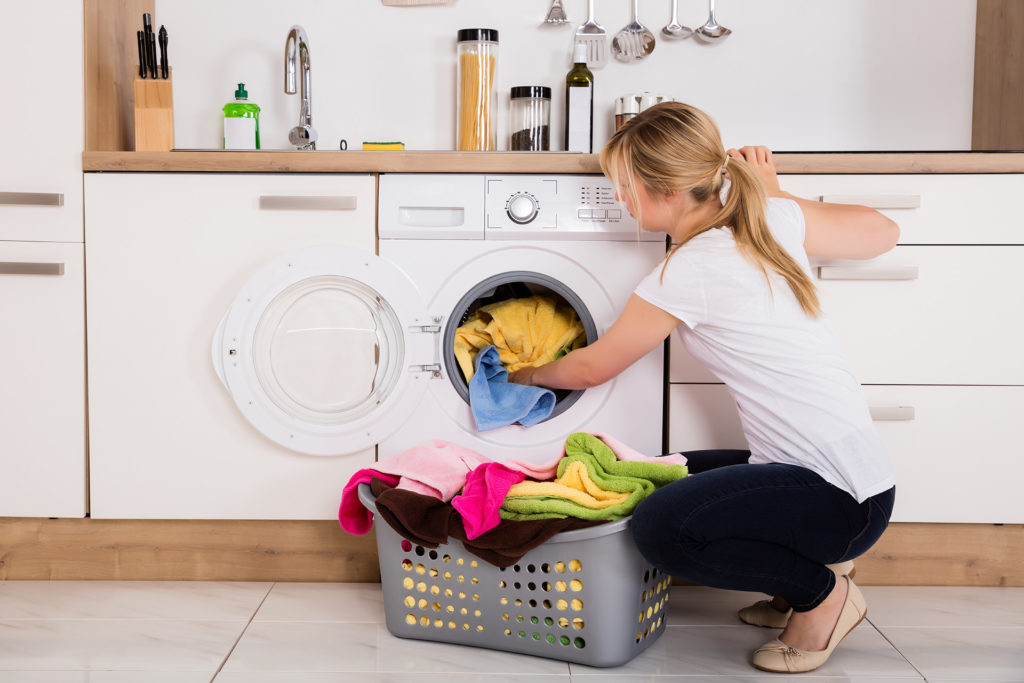 Young Woman Loading Clothes Into Washing Machine In Kitchen;