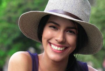 Woman wearing a straw hat in green garden