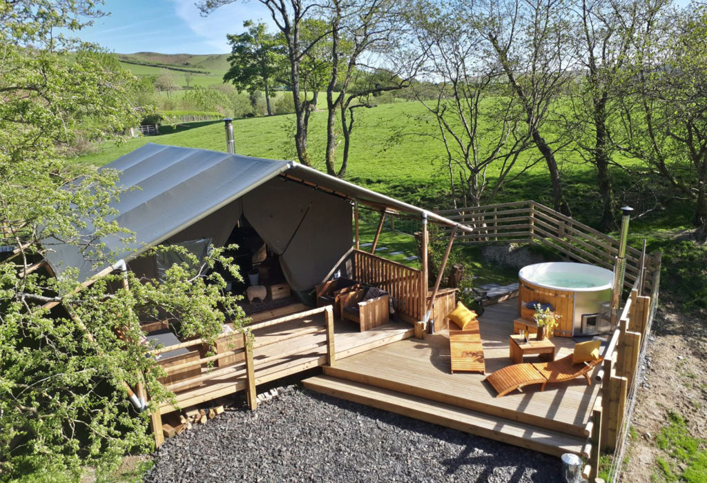 Tarpaulin roofed holiday chalet with loungers and hot tub on deck, countryside behind