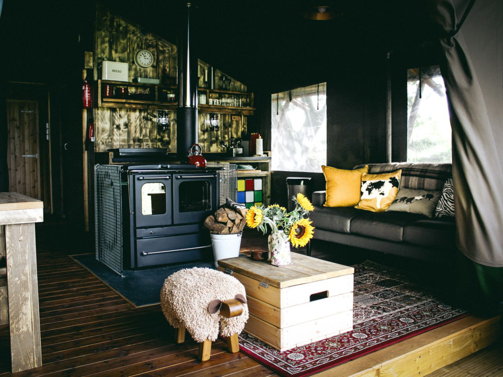 industrial/rustic interior with stove pipe, chunky wood, rug and child's sit-on sheep