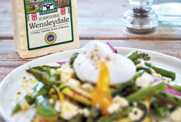 Plate of vegetables with crumbled cheese, poached egg and pack of Wensleydale cheese behind