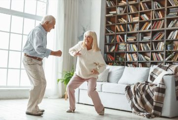 Senior couple together at home retirement concept dancing active dance playful