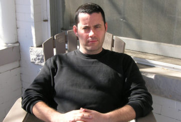 Crime writer Adrian McKinty sitting outside a house on a wooden chair, wearing plain black jumper