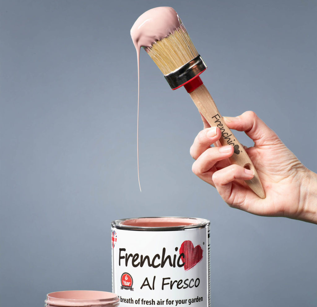 Pot of Frenchic Al Fresco brand paint in Dusky Pink. A woman's hand is holding a paintbrush that has been dipped in the thick, creamy paint.