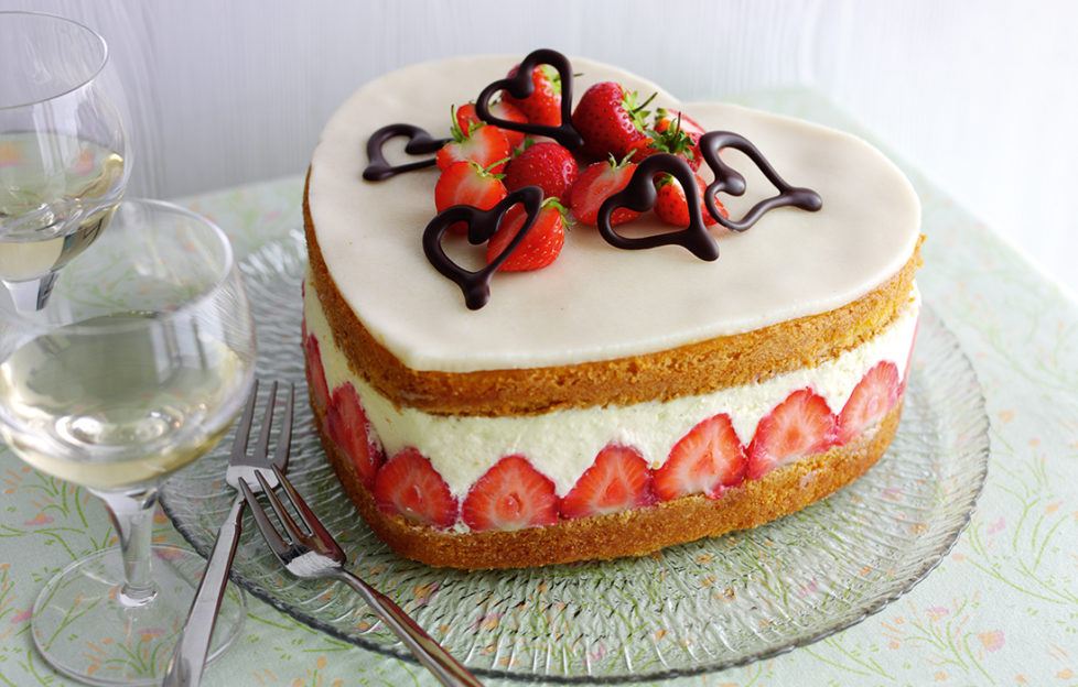 Heart shaped strawberry cake topped with white marzipan, strawberries and chocolate hearts. Between the sponge layers is a deep layer of set custard and a row of sliced strawberries arranged vertically.