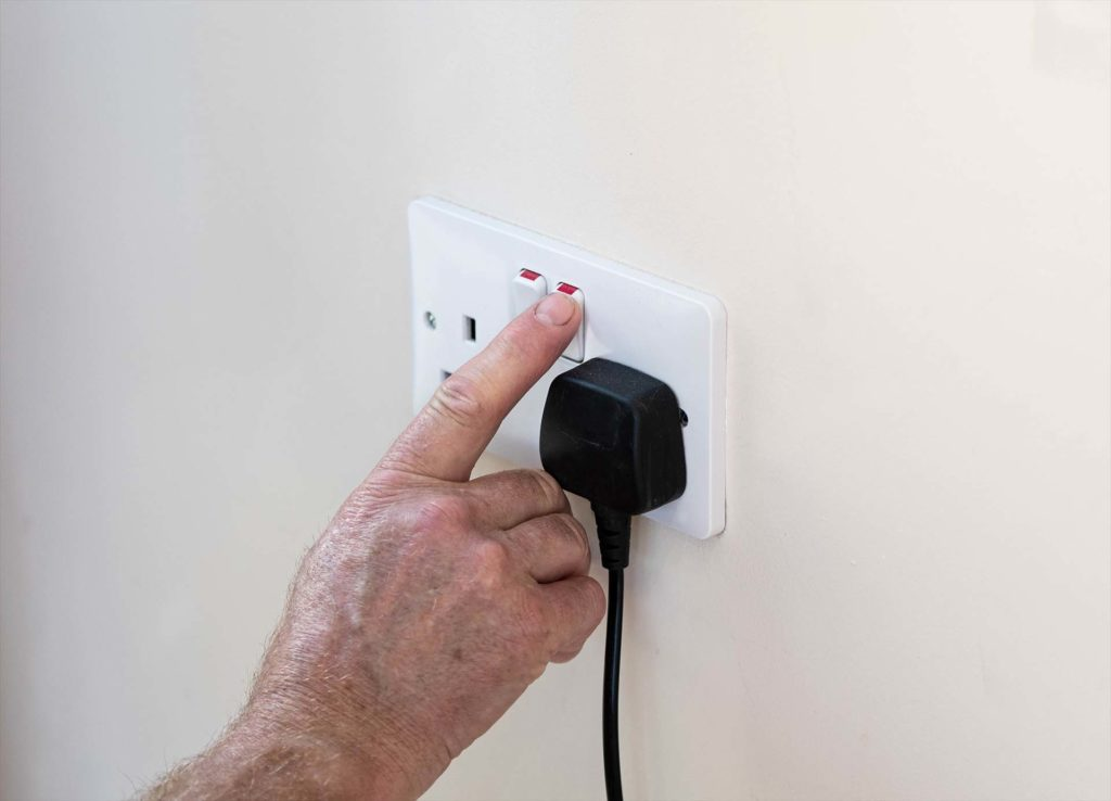 Mans hand turning off plug socket to save electricity and the planet