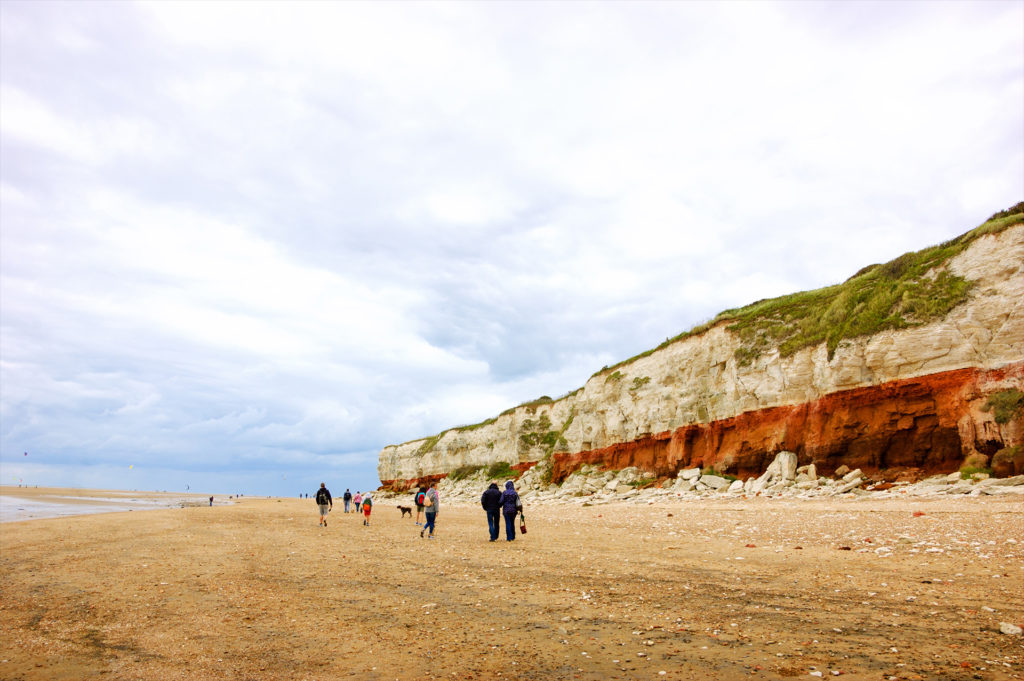 People walking Hunstanton cliffs beach. These famous red and white striped cliffs at Norfolk, UK are popular tourist attraction.