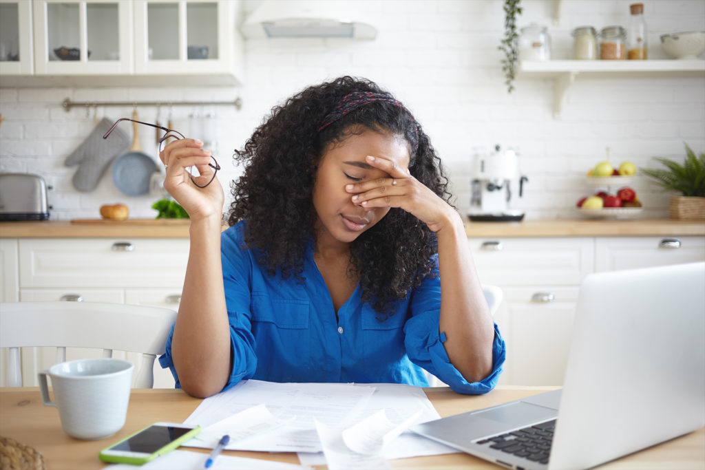 Tired young African American single mother feeling stressed because of financial problems, working through finances in kitchen late at night, doesn't have enough money to pay off mortage debt