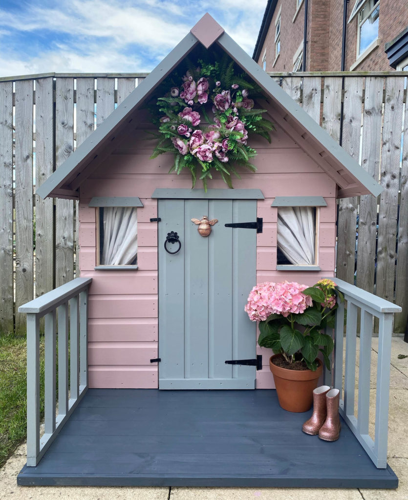 Cute wooden playhouse with banisters and wreath over door, painted in pink and grey