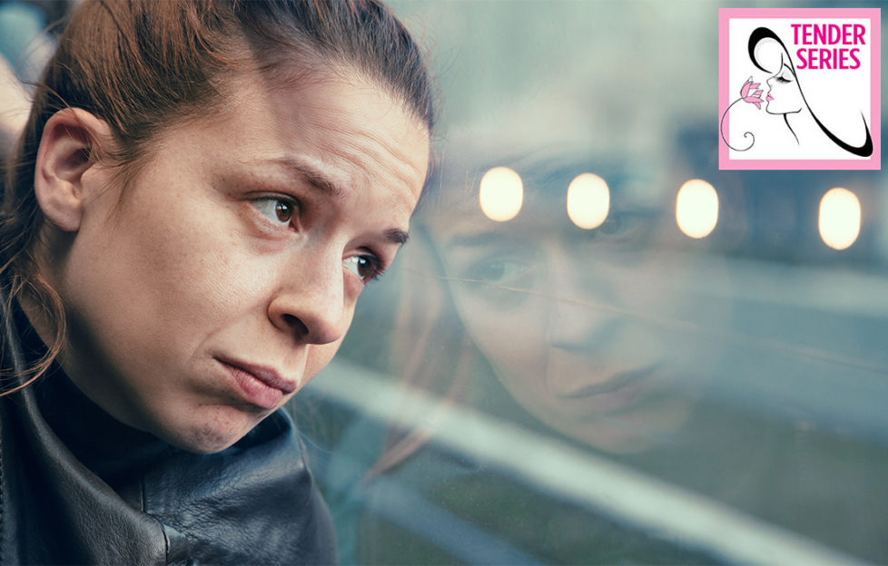 Worried woman looks out of bus window at grey rainy landscape and reflected lights