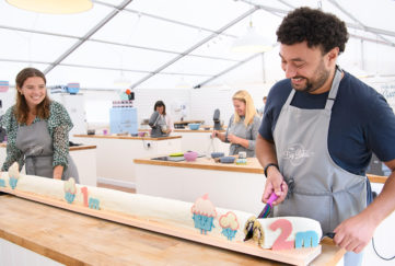 2 people in baking marquee cutting 2 metre long cake to show social distancing