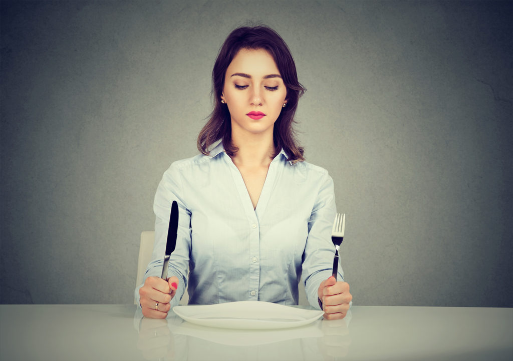 Serious woman with fork and knife sitting at table with empty plate isolated on gray wall background