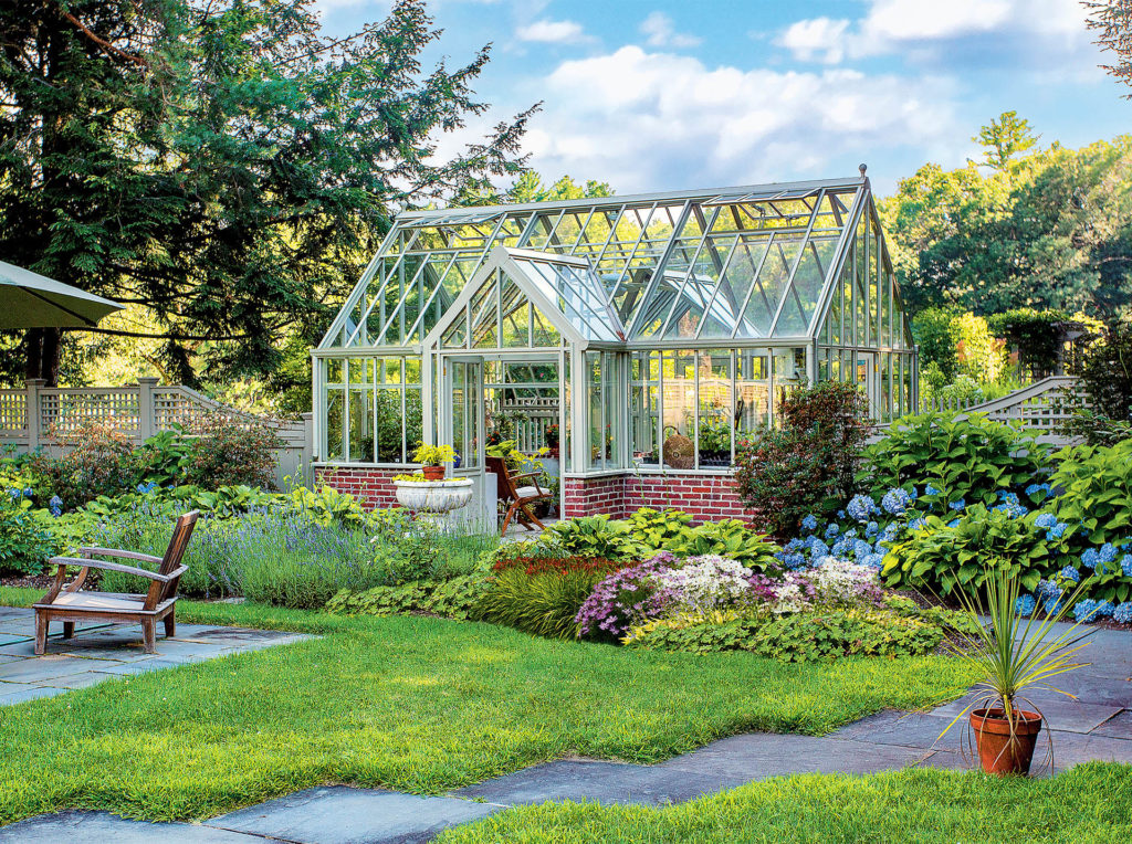 Victorian style greenhouse with several apexes, tall narrow glass panels, white frame, set in beautiful garden