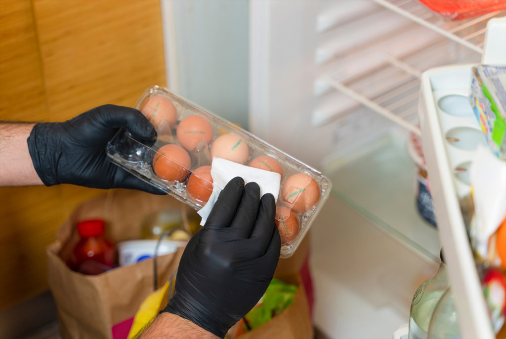 COVID-19: Is it necessary to clean your groceries delivered at home? Man in quarantine wiping plastic package with sanitizing wipes after shopping or receiving online delivery bags.