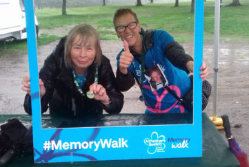 Two women show off their medals posing in a cardboard frame for Alzheimers Memory Walk, cold wet day