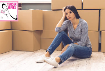 Woman moving away, piles of boxes, looks sad and wistful
