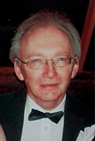 Head shot of smiling man with grey hair and glasses wearing a black bow tie and dinner jacket